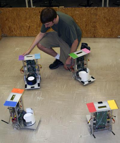 An overhead video camera allows a computer to recognize individual robots by their colored panels.