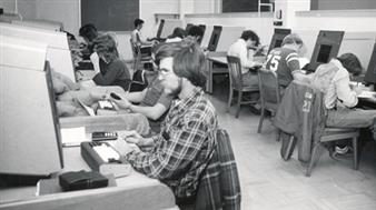 A PLATO lab in 1975; long-time Physics staff member, David D. Lesny, then a student, is seated at the first terminal.