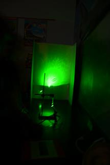 The students also investigated the science classroom's tap water, using a green laser pen and a drop of water as their microscope. By suspending a water droplet with an eyedropper and aiming a laser light through it, they projected the image of the water drop onto a white poster board. The students discovered that there is more than water coming out of the tap in the classroom! The water drop acts a spherical lense and gives a magnification of about 1000, which is sufficient to see microspic particles floating around. If you are curious and wish to know what is inside a drop of pond water, you can check out this video from Ann Arbor Scientific http://www.arborsci.com/deluxe-green-laser-pointer.
