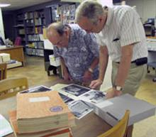 While at the University archives, ECE alumnus Wayne Lichtenberger (BSEE '55, MSEE '56, PhD '61) met with University Archivist William Maher (right), who brought out some ILLIAC material from the archive's collection. The books in the foreground are the code books Lichtenberger was donating.