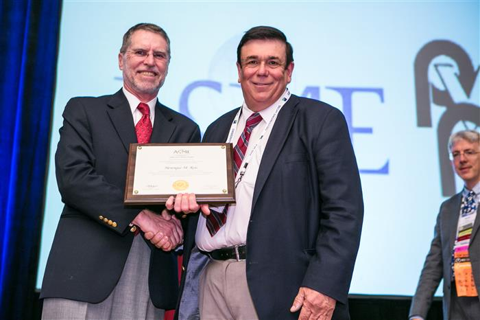 Professor Victor Giuriutiu from the University of South Carolina presenting the ASME award to Professor Reis