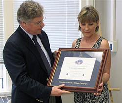 At a reception held June 20, ECE Department Head Andreas Cangellaris (left) presents Vicki Brown-Mowery with a certificate recognizing her 25 years of service to the University and the Department of Electrical and Computer Engineering.