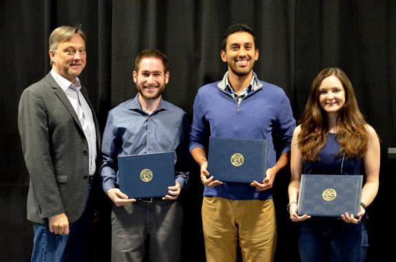 The LEXTECH Senior Design Most Marketable Project Award is presented to Mark Hafter, Omar Joya and Ellery Tomaszkiewicz  for their 'Collective Child Tracking System.' Also pictured: Professor Hutchinson.