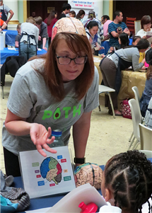 Linda Steinberg, a research coordinator at Illinois, speaks with a child during Brain Awareness Day near campus. (Photo by Ashley Lawrence, IHSI at Illinois.)