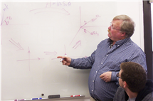 Bruce Carpenter, standing, associate director of instruction for NetMath, speaks to Matthew Garcia, a student who also worked as a mentor in the distance-learning program. (Photo courtesy of NetMath.)