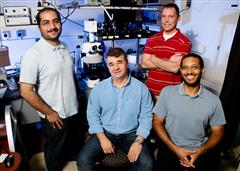 ECE researchers (from left, Amir Arbabi, Gabriel Popescu, Chris Edwards, and Lynford Goddard) use a special microscope to simultaneously etch tiny features in semiconductor wafers and monitor the process in real time. Photo by L. Brian Stauffer, U of I News Bureau.
