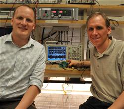 Assistant Professor Robert Pilawa and Christopher Barth at their PV research station. The solar panel below is attached to the buck converter in Barth's hand. At center, the screen shows the dithered ripple.
