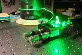 A sapphire-derived fiber is illuminated with a green laser beam on Dragic's custom-built optical breadboard.