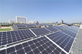 Team members finish work on the rooftop photovoltaic system. Photo by Guanxin He.