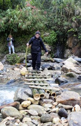 Project Leader Michele Niaki crosses a river at the site where the students are planning on building the bridge.