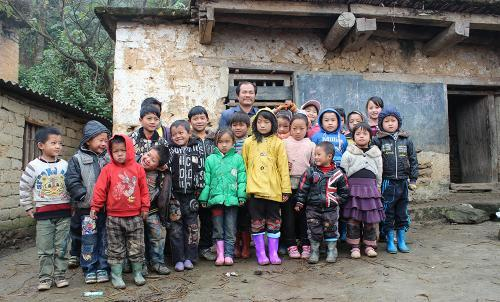 A school teacher from the Awhozu village stands with his class outside the school house.