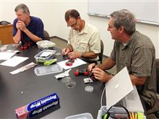 RET teachers Dan Reid, David Bergandine and Terry Koker (left to right) test their solar cells.