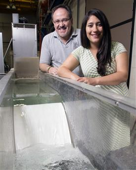 CEE professor Marcelo Garcia and USGS research hydrologist Tatiana Garcia with a physical model of a low head dam in the Ven T. Chow Hydrosystems Laboratory that represents Asian carp spawning location.