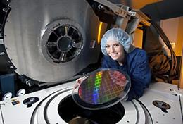 IBM test engineer and ECE alumna Sara Lestage (BSEE '99) holds a 300-mm Power 7 processor wafer next to a wafer test tool.