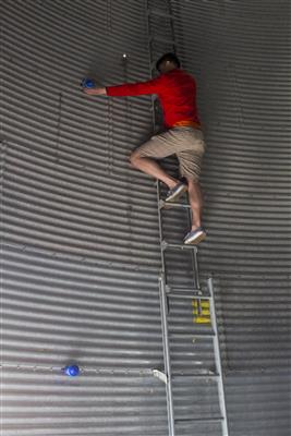 A team member installs sensors in an empty grain bin.