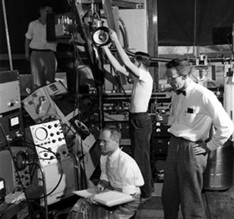 From the Illinois Alumni News, Vol. 36, No. 3 (April 1957). 'This apparatus on the first floor of the Physics Laboratory looks complex. It doesn't seem so to these physicists: at right, Prof. Dillon E. Mapother; seated with notebook, Prof. J.C. Wheatley; standing in the center of the picture, Thomas Estle, and at back and left, Howard Hart. Estle is an Eastman Kodak fellow and Hart a National Science Foundation fellow. The apparatus includes a cryostat in which temperatures within a few thousandths of one degree of absolute zero (about 459 below zero Fahrenheit) are produced by a process know as adiabatic demagnetization. At low temperatures, materials take on very unusual properties, the study of which often gives special insight into the internal structure, forces and processes in nature.' Photo courtesy University of Illinois Alumni Association.