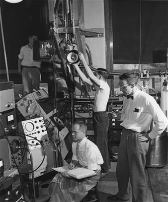 Wheatley–Mapother low-temp lab, 1957  From the Illinois Alumni News, Vol. 36, No. 3 (April 1957). 'This apparatus on the first floor of the Physics Laboratory looks complex. It doesn't seem so to these physicists: at right, Prof. Dillon E. Mapother; seated with notebook, Prof. J.C. Wheatley; standing in the center of the picture, Thomas Estle, and at back and left, Howard Hart. Estle is an Eastman Kodak fellow and Hart a National Science Foundation fellow. The apparatus includes a cryostat in which temperatures within a few thousandths of one degree of absolute zero (about 459 below zero Fahrenheit) are produced by a process know as adiabatic demagnetization. At low temperatures, materials take on very unusual properties, the study of which often gives special insight into the internal structure, forces and processes in nature.'  Please credit the photo to: University of Illinois Alumni Association Archives