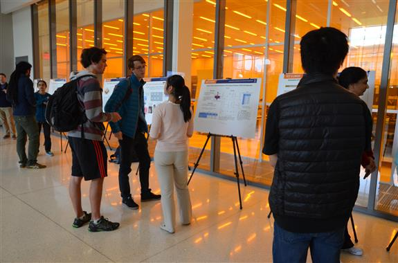 Graduate Research Assistant Fu Sun discusses her poster on 'Effects of Spin Coating Parameters on the Coating Thickness of SPR-220 Photoresistor' with some ECE students.