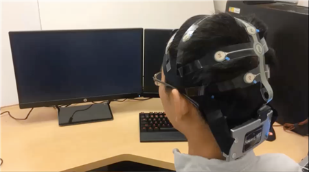 PhD student Yao Li demonstrates the technology which uses brain control interface to send signals to a robot.