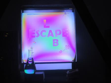Chiral corn-syrup molecules polarize light, in a tank with the LabEscape logo.