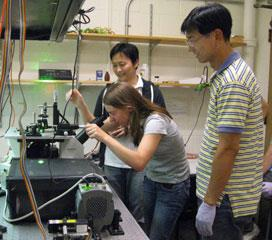 CPLC postdoctoral fellow, Hajin Kim (rear) training 2011 summer school students, Jessica Killian and Jinrang Kim in single-molecule total internal reflection fluorescence microscopy.
