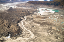 A stream runs along the toe of Kaskawulsh Glacer in Kluane National Park, Yukon. In 2016, this channel allowed the glacier's meltwater to drain in a different direction than normal, resulting in the Slims River water being rerouted to a different river system. (Photo by Dan Shugar, University of Washington Tacoma.)
