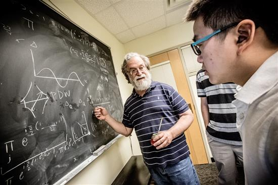 Eduardo Fradkin, a professor of physics and director of the Institute for Condensed Matter Theory (ICMT) at the University of Illinois at Urbana-Champaign, works with theoretical condensed matter grad students in his group, at the ICMT. Photo by L. Brian Stauffer, University of Illinois at Urbana-Champaign