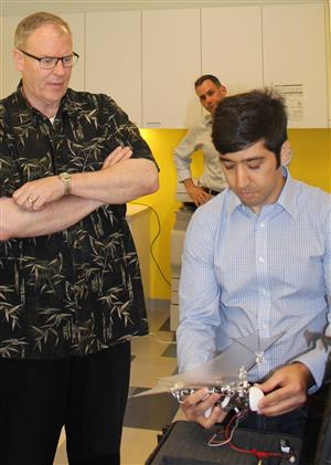 U.S. Deputy Secretary of Defense Bob Work observes a 'bat bot' demonstrated by postdoctoral researcher Alireza Ramezani in the Coordinated Science Lab.