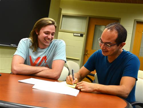 Associate Professor of Physics Taylor Hughes works with graduate student Wladimir Benalcazar at the Institute for Condensed Matter Theory. Photo by Siv Schwink, Department of Physics, University of Illinois at Urbana-Champaign.