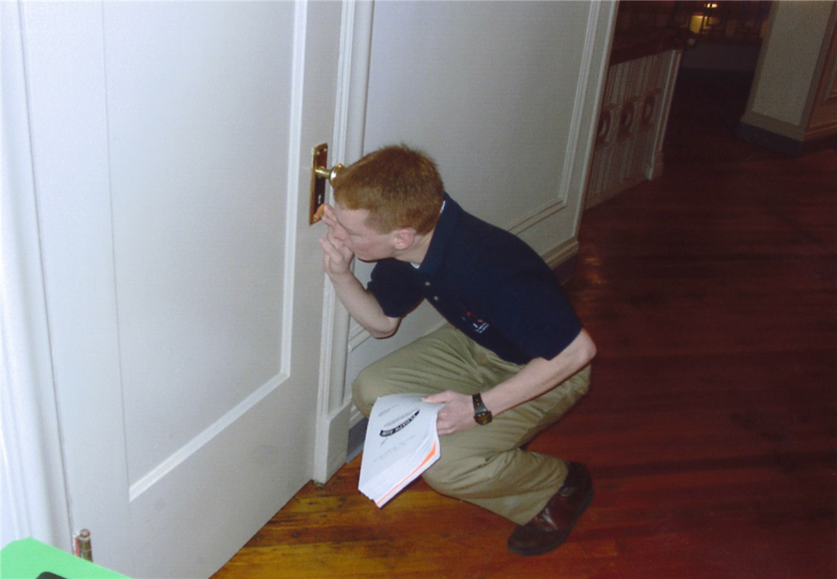Student kneels down by a doorknob