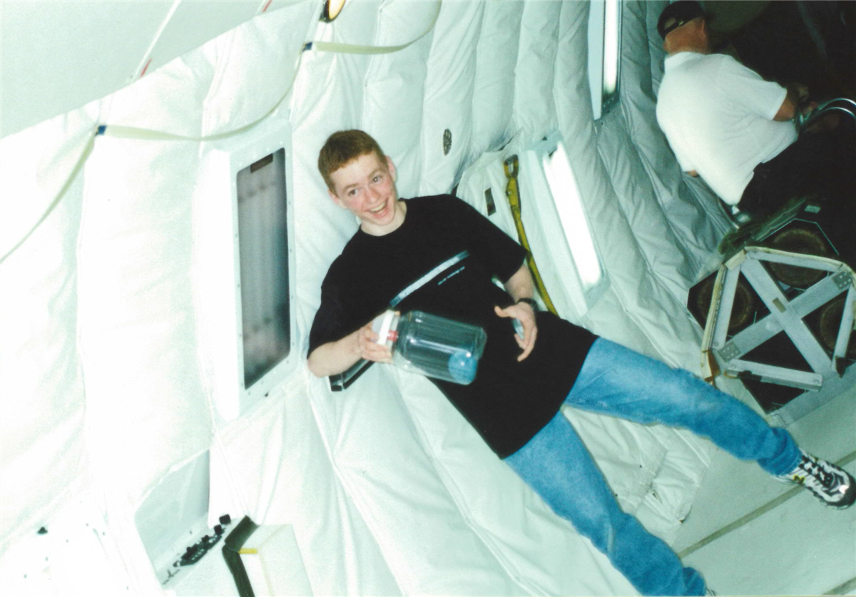 A student on the airplane prepares for a low gravity environment
