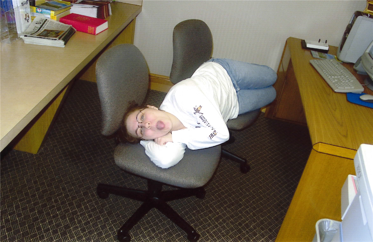 A student lays across two chairs