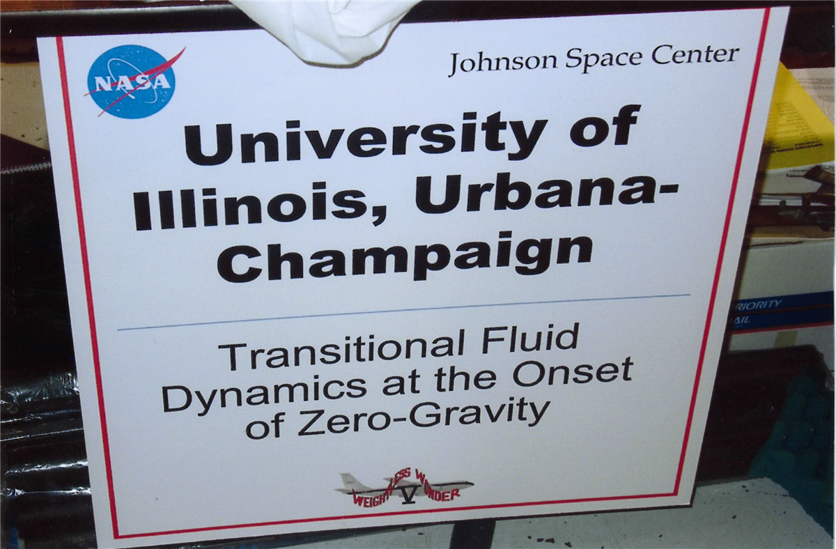 Sign reads: Johnson Space Center University of Illinois, Urbana-Champaign Transitional Fluid Dynamics at the Onset of Zero-Gravity