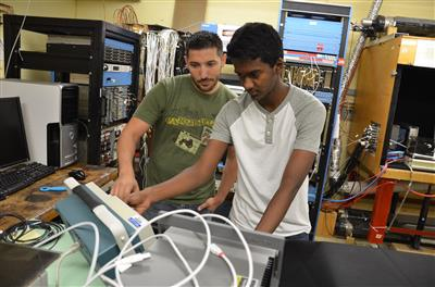 Mentor Chad Lantz and Young Scholar Sibiraj Senguttuvan (right) work on testing an LHC detector in Matthias Grosse Perdekamp's lab.
