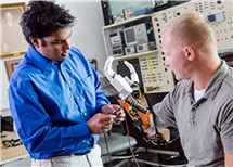 Aadeel Akhtar assisting amputee Sgt. Garrett Anderson. Credit: PSYONIC's website.