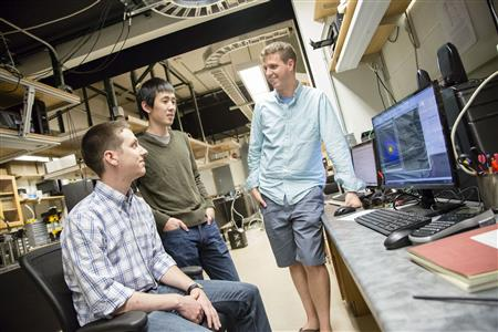 Assistant Professor Bryce Gadway meets with graduate students in his laboratory in the Loomis Laboratory of Physics.
