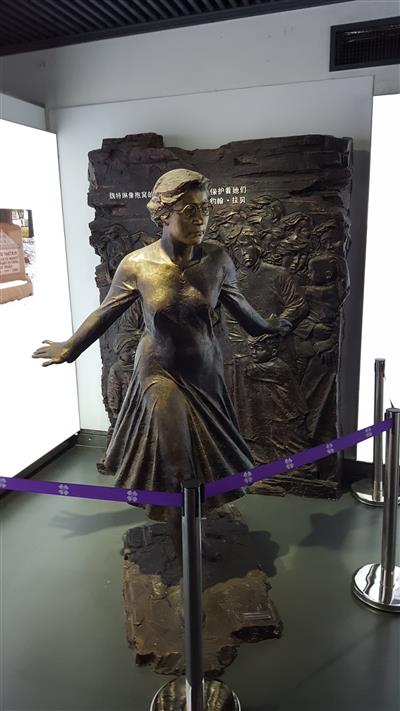 Minnie Vautrin Statue at the Nanjing Massacre Memorial Museum in Nanjing, China. Vautrin is a native of Secor, Illinois and a U of I alumna, class of 1912, who saved more than 10,000 girls and woman during the Nanjing Massacre from December 1937 to February 1938. The statue shows Vautrin protecting Chinese civilians who are displayed on the relief in the back. In Nanjing Minnie Vautrin is known as the 'Goddess of Mercy for Women and Children in Nanjing.' Location: Nanjing Massacre Memorial Museum in Nanjing, China. Photo by: Matthias Grosse Perdekamp, July 28, 2017