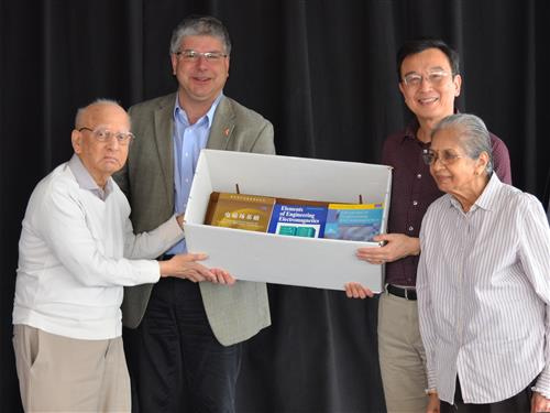 Professor Emeritus Rao (left) and his wife Sarojini (right), present ECE Department Head William H. Sanders and Professor Wen-mei Hwu, ECE Faculty Advisory Committee Chair, with copies of his books.
