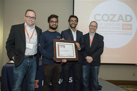 Vitrix Health won the 2018 Cozad New Venture Competition. Technology Entrepreneur Center director Andy Singer (right) and TEC director of operations Jed Taylor (left) join Vitrix Health co-founders Ayush Kumar (second from left) and Aashay Patel (second from right) on stage during the awards presentation.