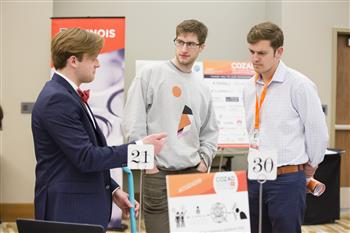 Previous winners Lucas Frye (far right, Amber Agriculture) and Sam Walder (middle, Trala) learn about Go-Go Garden tools from founder Thomas Suppes.
