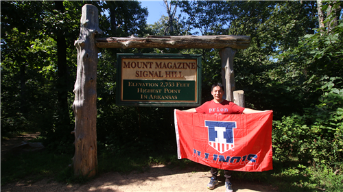 Yue in Arkansas with a University of Illinois flag at Mount Magazine State Park's high point, Signal Hill.