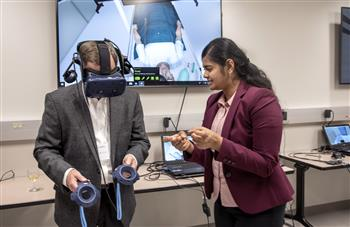 Pavithra Rajeswaran, research engineer for the Healthcare Engineering Systems Center, helps guide a visitor through a Virtual Reality demonstration during the Jump Simulation Open House on July 27.