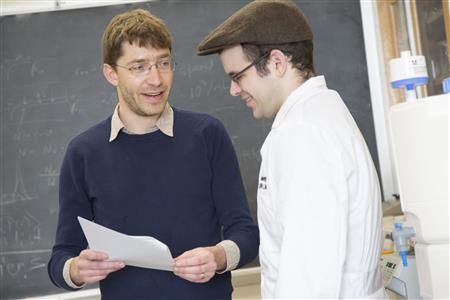 Professor Seppe Kuehn (left) and graduate student Jason Merritt confer in the Loomis Laboratory of Physics in Urbana. Photo by L. Brian Stauffer, University of Illinois at Urbana-Champaign
