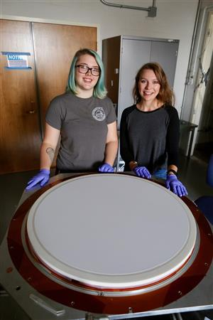 U of I physics undergraduate student Anna Koffman poses with REU student Sierra Barone from Wheaton College, in the Vieira lab, summer 2017. In the foreground is a large lens with a specially developed anti-reflection coating for the South Pole Telescope 3G Camera. Koffman is now a graduate student at the University of Pennsylvania.