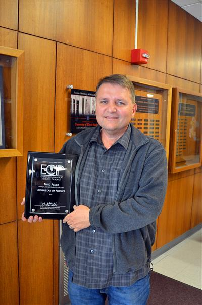 Illinois Physics facilities manager Jerry Cook holds the ECIP energy conservation award plaque to be mounted in the Walnut Hallway.
