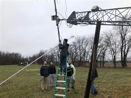 U of I engineering students Dillon Hammond, Rong Zhou Li, Adam Newhouse, Robert Maksimowicz, and Rick Eason inspect the ground station antenna in preparation for CubeSail mission operations. The ground station is located north of Urbana and will be used for sending commands and receiving telemetry from CubeSail.