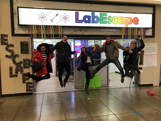 LabEscape participants jump for joy after successfully completing their mission at Lincoln Square Mall in Urbana.