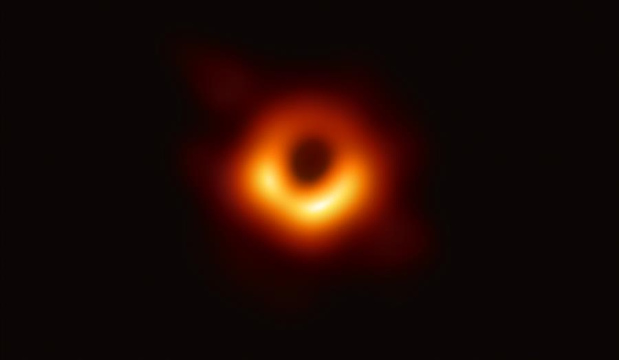 First Image of a Black Hole. The shadow of a black hole seen here is the closest we can come to an image of the black hole itself, a completely dark object from which light cannot escape. The black hole's boundary — the event horizon from which the EHT takes its name — is around 2.5 times smaller than the shadow it casts and measures just under 40 billion km across. While this may sound large, this ring is only about 40 microarcseconds across — equivalent to measuring the length of a credit card on the surface of the Moon. CREDIT: EHT Collaboration