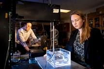 Gun Kim and Abigail Halmes work on equipment that emits an ultrasound wave inducing a reaction that produces light in synthetic molecules.