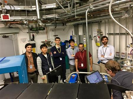 Professor Peter Abbamonte (middle, in navy sweater) and postdoctoral researcher Matteo Mitrano (right, in white dress shirt) pose with their team at the SLAC National Accelerator Laboratory in Menlo Park, California. The experimental team used a new investigative technique called time-resolved resonant soft x-ray scattering, to probe the striped charge order phase in a well-studied cuprate superconductor, with an unprecedented energy resolution, finding that superconductivity in cuprates may be mediated by charge-order fluctuations. This is the first time such an experiment has been done at an energy scale relevant to superconductivity. Source: SLAC